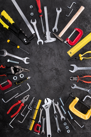 Top view of set of construction tools on black background
