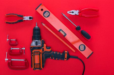 Draufsicht auf verschiedene Werkstücke und Bleistift auf Rot
