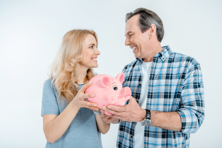 Front view of happy couple holding piggy bank
