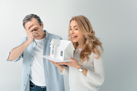 homeowners: happy woman holding house model with husband near by on grey Stock Photo