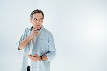 mature man holding digital tablet and looking away on grey