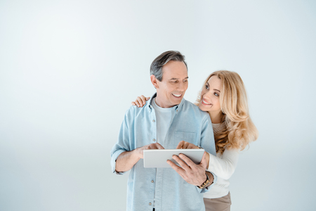 middle aged couple standing embracing and using digital tablet on grey