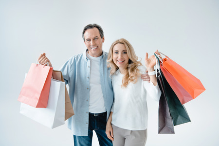 middle aged couple holding shopping bags and smiling at camera