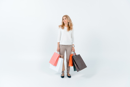blonde woman holding shopping bags and looking away on grey