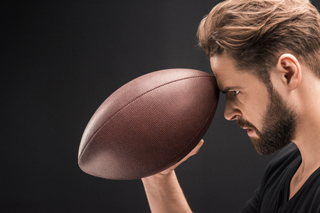 man profile: angry bearded man holding rugby ball on black