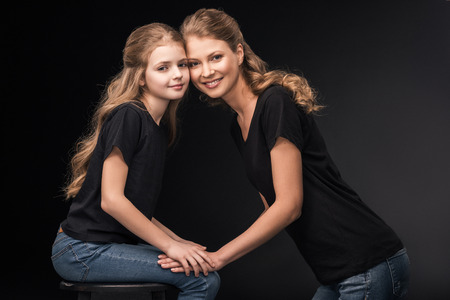 happy mother and daughter holding hands and smiling at camera Stock Photo