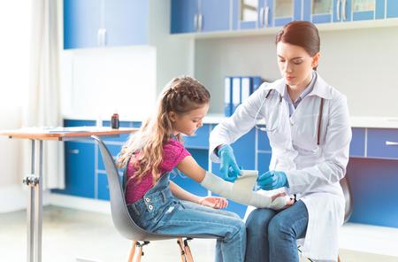 Doctor vendaje de mano de niña en el hospital Foto de archivo - 76606569
