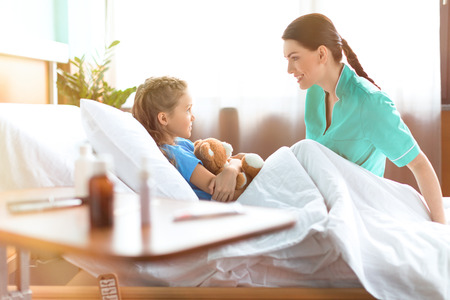 petite fille allongée dans un lit d'hôpital avec un ours en peluche et de parler avec une infirmière souriante