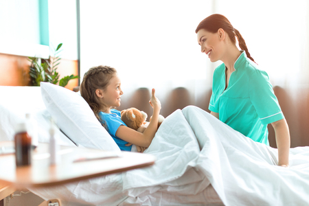 little girl lying in hospital bed with teddy bear and talking with smiling nurse