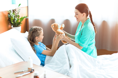 girl and nurse holding teddy bear in hospital room Stok Fotoğraf
