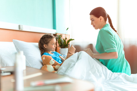 Doctor and little patient with teddy bear lying on bed