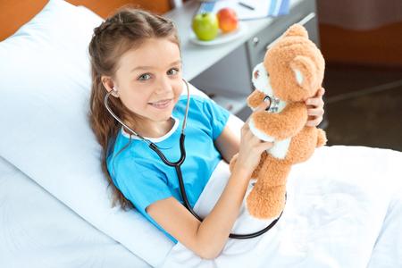 patient with stethoscope and teddy bear lying on bed in hospital