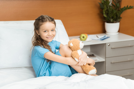 patient with teddy bear sitting on bed in hospital