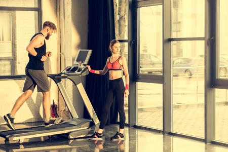 sporty woman standing near bearded sportsman training on treadmill