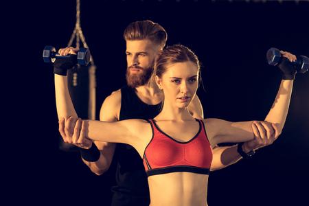 ダンベルを持つハンサムな男性トレーニング スポーティな若い女性