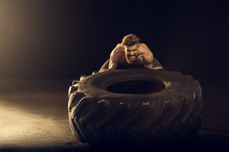 muscular sportsman training with big tire on black with side lighting