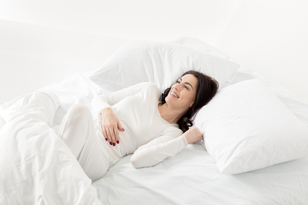 woman in white sleepwear awakening in bed at home