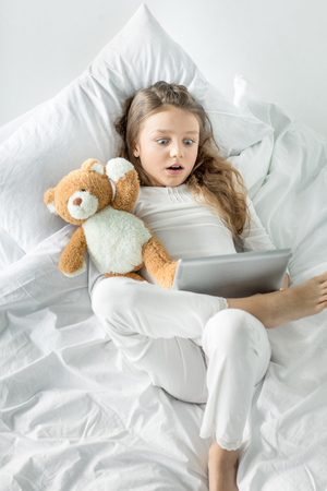 little girl in pajamas using digital tablet while lying in bed