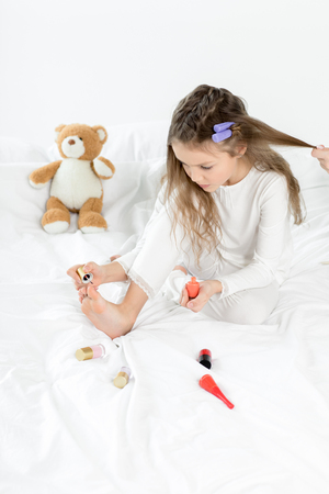 little girl in pajamas and curlers applying nail polish to toenails sitting on bed