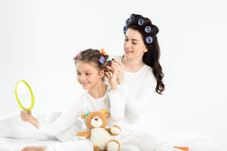 mother in curlers curling hair to happy little daughter looking at hand mirror