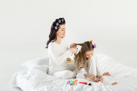 mother curling hair to daughter applying nail polish while sitting on bed Stock Photo