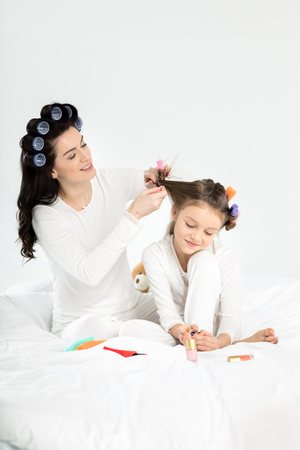 Mother curling hair to daughter applying nail polish on toenails Stock Photo