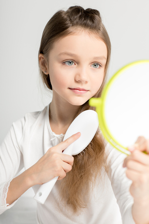 cute little girl holding hand mirror and combing hair