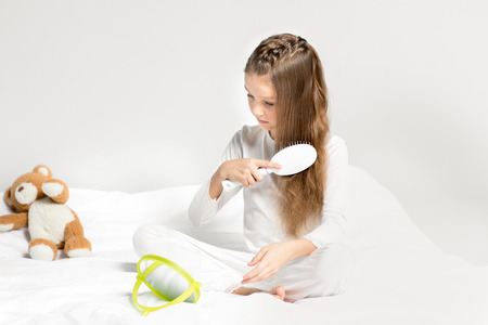 little girl in pajamas sitting on bed and combing hair Stock Photo