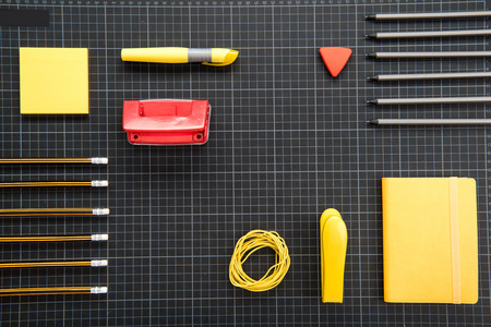 organized various office supplies on black background