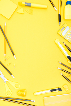 Flat lay of yellow office supplies, calculator and pencils with copy space