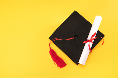 Top view of graduation mortarboard and diploma on yellow background