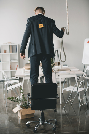 fired businessman standing on chair and trying to hang himself in office