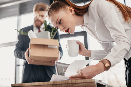 concentrated businesswoman with documents and upset fired businessman with cardboard box behind