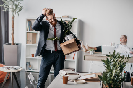 upset fired businessman with cardboard box in office, boss behind