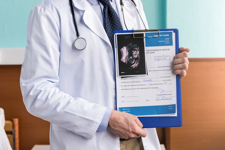 man doctor holding clipboard with medical diagnosis and ultrasound scan