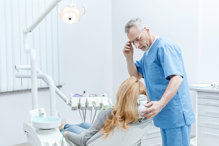dentist in uniform talking with patient in dental clinic
