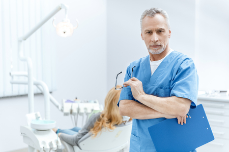 dentist in uniform with clipboard in dental clinic with patient behind