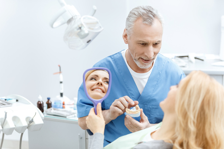 dentist showing jaws model to patient Stock Photo