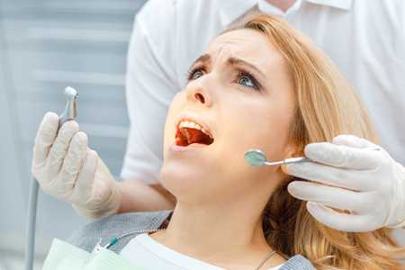 dentist curing scared patient looking up Stock Photo