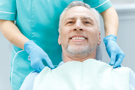 笑顔の成熟した患者と医療用手袋の歯医者 写真素材
