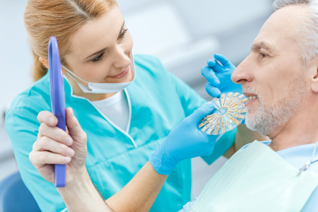 dentist with samples comparing teeth of mature patient looking at mirror