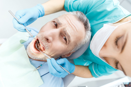 professional dentist curing scared mature patient in dental clinic