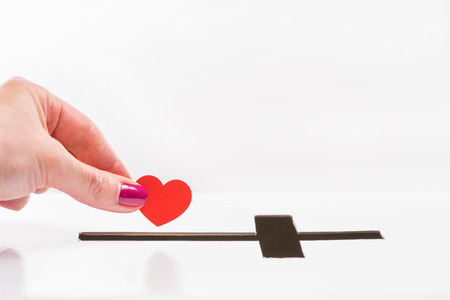 Close-up partial view of woman inserting red heart symbol into hole for donations in form of cross, donation and faith concept Stock Photo