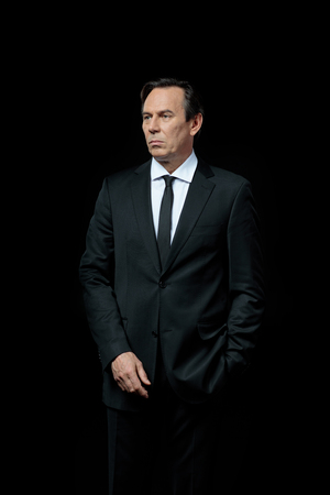 Serious mature businessman in suit looking away
