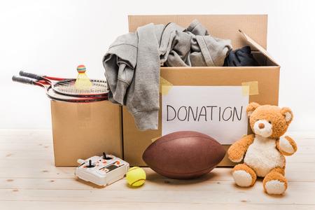 kartonnen dozen met donatiekleding en verschillende voorwerpen op wit, donatieconcept