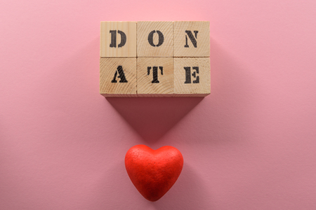 Close-up top view of wooden cubes with word donate and red heart symbol, donation concept
