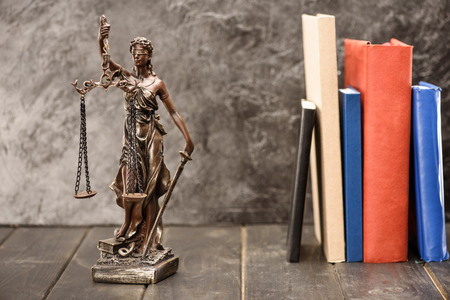 Close-up view of antique statue of lady justice and books, Law concept Фото со стока