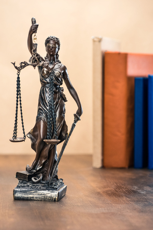 Close-up view of statue of lady justice on wooden table, Law concept