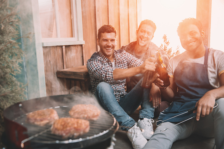 young friends making barbecue and drinking beer on porch with back light Stock Photo