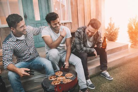 Jonge vrienden drinken bier en plezier tijdens het maken van barbecue